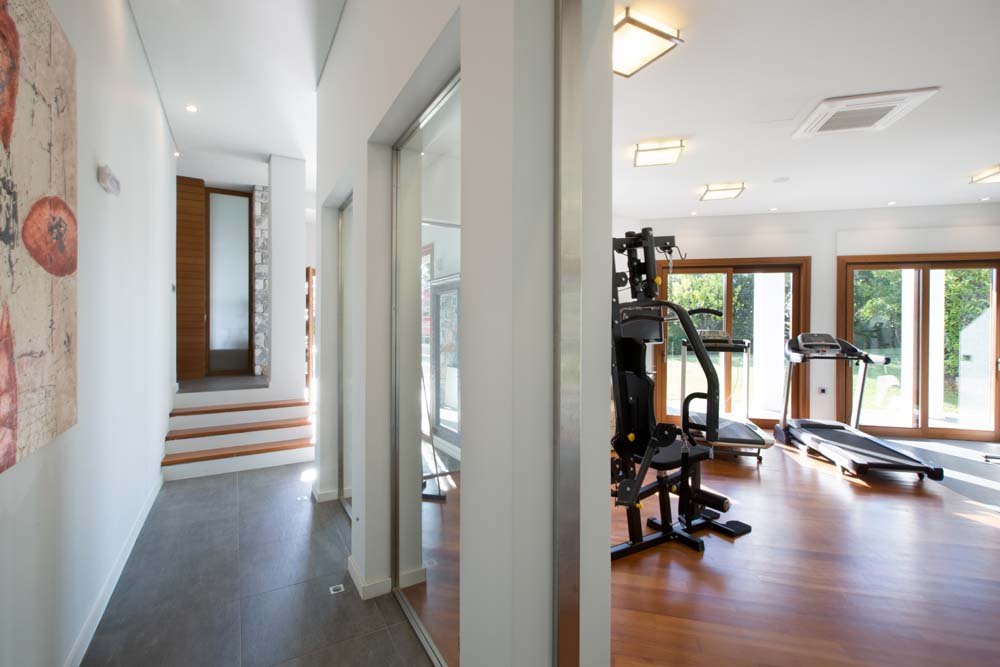 Gym with natural light and garden views
